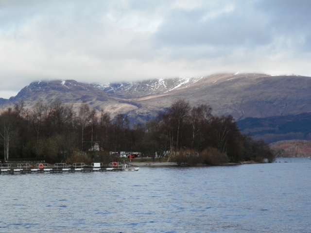 Ben Lomond shrouded by clouds overlooking Loch Lomond at Luss
